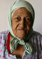 An aging woman is seen at a retirement home in Sadr City, Baghdad, Iraq, July 22, 2003. Even though most families in Iraq care for their aging relatives at home, there is still a need for the facility, which is the largest of its kind in Baghdad housing 45 women and 87 men. The facility was not looted during the war, but it is still lacks some funding and is in need of medications for patients with chronic conditions such as heart disease and diabetes.
