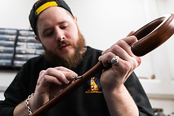 Umbrella maker Lee files off the rough edges on a rosewood shaft after cutting grooves for the umbrella's retaining springs. Craftspeople at Fox Umbrellas Ltd, a company in Croydon, Surrey, that has been going for over 150 years hand build quality umbrellas. Croydon, Surrey, March 06 2019.