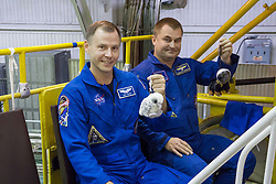 """At the Baikonur Cosmodrome in Kazakhstan, Expedition 57 crewmembers Nick Hague of NASA (left) and Alexey Ovchinin of Roscosmos (right) hold up toy mascots Oct. 6 during final fit check activities prior to launch. The mascots will be mounted over their heads in the Soyuz MS-10 spacecraft to serve as """"zero-G"""" indicators when they launch Oct. 11 for a six-month mission on the International Space Station.<br /> <br /> NASA/Victor Zelentsov"""