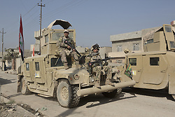 November 11, 2016 - Mosul, Nineveh, Iraq - 11/11/2016. Mosul, Iraq. Soldiers, of the Iraqi Army's 9th Armoured Division, sit on an armoured Humvee as it drives along a road during a visit to Mosul's Al Inisar district on the south east of the city. The Al Intisar district was taken four days ago by Iraqi Security Forces (ISF) and, despite its proximity to ongoing fighting between ISF and ISIS militants, many residents still live in the settlement without regular power and water and with dwindling food supplies...The battle to retake Mosul, which fell June 2014, started on the 16th of October 2016 with Iraqi Security Forces eventually reaching the city on the 1st of November. Since then elements of the Iraq Army and Police have succeeded in pushing into the city and retaking several neighbourhoods allowing civilians living there to be evacuated - though many more remain trapped within Mosul. (Credit Image: © Matt Cetti-Roberts via ZUMA Wire)