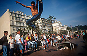 A 1990s Cote dAzur skater performs a high stunt leap in front of a crowd of admirers on the Promenade de Anglais, on 10th May 1996, in Nice, France.