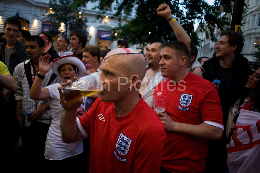 During a televised TV screening in a West End pub, England World Cup football fans have gathered to watch their team's opening match versus USA on TV in London. A bald-headed man is with his drunken partner and he drinks a pint of beer as his mates dance and sing a known football anthem. Dressed in fashionably similar England shirts - complete with the epic Three Lions badge, worn on the team's chests since their 1966 victory - the last national victory. Much alcohol (mostly, lager beer) is consumed and noisy, loutish behaviour can be heard in the capital's streets.
