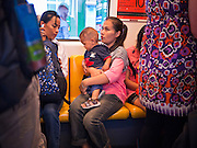 14 JULY 2011 - BANGKOK, THAILAND:   A woman and her child on the BTS Skytrain in Bangkok. The Bangkok Mass Transit System, commonly known as the BTS Skytrain, is an elevated rapid transit system in Bangkok, Thailand. It is operated by Bangkok Mass Transit System Public Company Limited (BTSC) under a concession granted by the Bangkok Metropolitan Administration (BMA). The system consists of twenty-three stations along two lines: the Sukhumvit line running northwards and eastwards, terminating at Mo Chit and On Nut respectively, and the Silom line which plies Silom and Sathon Roads, the Central Business District of Bangkok, terminating at the National Stadium and Wongwian Yai. The lines interchange at Siam Station and have a combined route distance of 55 km.    PHOTO BY JACK KURTZ
