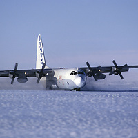 ANTARCTICA. Wheeled C-130 Hercules lands on ice runway at Patriot Hills expedition base in Ellsworth Mountains.