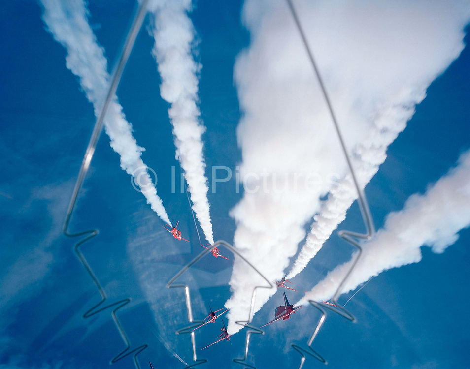 Some of the nine Hawk jet aircraft of the elite 'Red Arrows', Britain's prestigious Royal Air Force aerobatic team, perform the 5/4 Split high during an In-Season Practice (ISP) training flight near their base at RAF Scampton. Seen through the explosive Plexiglass cockpit of a tenth plane, we see forward into deep blue sky as two sets of aerobatic pilots steer their machines from a crossover manoeuvre, their organic white smoke pouring from their jet pipes to emphasize their paths through the air. In front of a local crowd at the airfield the team work their way through a 25-minute series of display manoeuvres that are loved by thousands at summer air shows. After some time off, spare days like this are used to hone their manual aerobatic and piloting skills before re-joining the air show circuit. Since 1965 they've flown over 4,000 shows in 52 countries.