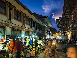 October 11, 2016 - Ubud, Bali, Indonesia - People shop and walk through the market in Ubud just before sunrise. The morning market in Ubud is for produce and meat and serves local people from about 4:30 AM until about 7:30 AM. As the morning progresses the local vendors pack up and leave and vendors selling tourist curios move in. By about 8:30 AM the market is mostly a tourist market selling curios to tourists. Ubud is Bali's art and cultural center. (Credit Image: © Jack Kurtz via ZUMA Wire)