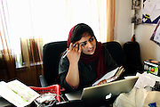 Alka Sadat, 24, (centre), an award-winning documentary and fiction filmmaker, is smiling while sitting at her desk in Kabul, Afghanistan.