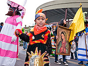 """03 DECEMBER 2011 - PHOENIX, AZ:    Children in a procession to honor the Virgin of Guadalupe in Phoenix Saturday. The Phoenix diocese of the Roman Catholic Church held its Sixth Annual Honor Your Mother Day Saturday to honor the Virgin of Guadalupe. According to Mexican Catholic tradition, on December 9, 1531 Juan Diego, an indigenous peasant, had a vision of a young woman while he was on a hill in the Tepeyac desert, near Mexico City. The woman told him to build a church exactly on the spot where they were standing. He told the local bishop, who asked for some proof. He went back and had the vision again. He told the lady that the bishop wanted proof, and she said """"Bring the roses behind you."""" Turning to look, he found a rose bush growing behind him. He cut the roses, placed them in his poncho and returned to the bishop, saying he had brought proof. When he opened his poncho, instead of roses, there was an image of the young lady in the vision. The Virgin is now honored on Dec 12 in Catholic churches throughout Latin America and in Hispanic communitied in the US.   PHOTO BY JACK KURTZ"""