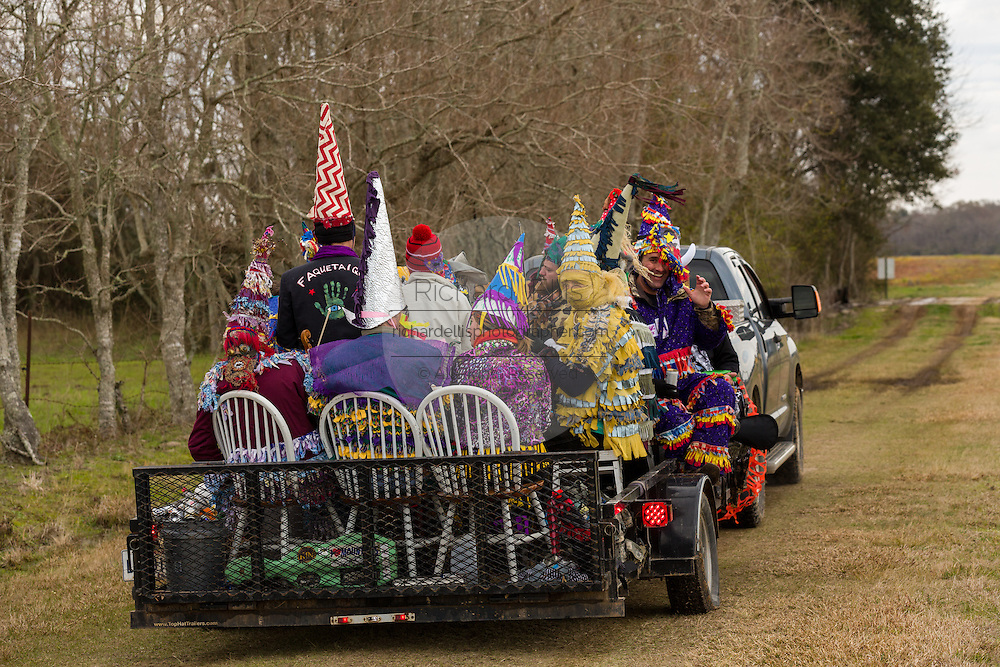 Cajun Mardi Gras revelers ride through the countryside going house to house during the Faquetigue Courir de Mardi Gras chicken run on Fat Tuesday February 17, 2015 in Eunice, Louisiana. The traditional Cajun Mardi Gras involves costumed revelers competing to catch a live chicken as they move from house to house throughout the rural community.