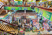 """12 APRIL 2012 - HO CHI MINH CITY, VIETNAM: Overview of an interior aisle in Binh Tay Market. The market is warren of narrow halls and alleys and steep staircases and still relies on manual labor to move goods. Binh Tay market is the largest market in Ho Chi Minh City and is the central market of Cholon. Cholon is the Chinese-influenced section of Ho Chi Minh City (former Saigon). It is the largest """"Chinatown"""" in Vietnam. Cholon consists of the western half of District 5 as well as several adjoining neighborhoods in District 6. The Vietnamese name Cholon literally means """"big"""" (lon) """"market"""" (cho). Incorporated in 1879 as a city 11km from central Saigon. By the 1930s, it had expanded to the city limit of Saigon. On April 27, 1931, French colonial authorities merged the two cities to form Saigon-Cholon. In 1956, """"Cholon"""" was dropped from the name and the city became known as Saigon. During the Vietnam War (called the American War by the Vietnamese), soldiers and deserters from the United States Army maintained a thriving black market in Cholon, trading in various American and especially U.S Army-issue items.     PHOTO BY JACK KURTZ"""