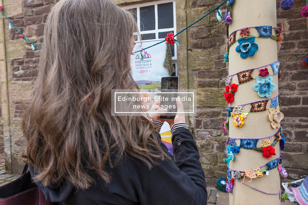 Yarn-bombing during the Scotland-wide World Heritage Day festivities. Six unique events, coordinated by Dig It! 2017, celebrated Scotland's six World Heritage Sites as part of the 2017 Year of History, Heritage and Archaeology. <br /> <br /> Pictured: An on-looker takes photos of the photo-bombing