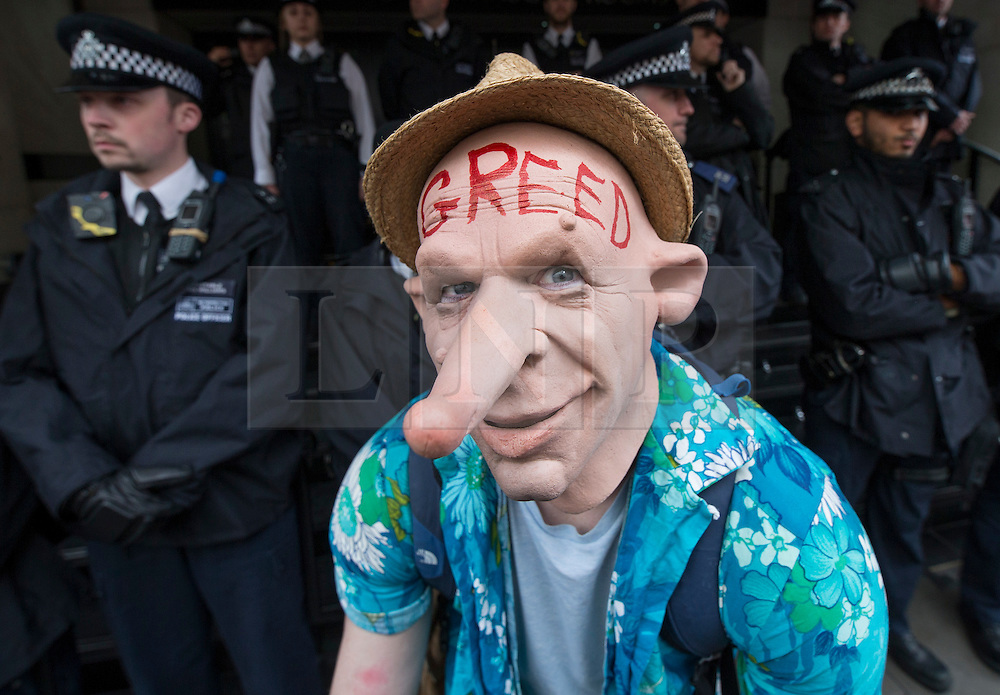 © Licensed to London News Pictures. 09/04/2016. London, UK. A tax reform demonstrator poses in front of police guarding the Conservative Spring Conference at the Connaught Rooms. Photo credit: Peter Macdiarmid/LNP
