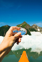 Viewing the mountain and kayak reflections in a piece of ice from an iceberg at Bear Glacier, Kenai Fjords National Park, Alaska