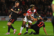 Mallik Wilks of Doncaster Rovers (7) is fouled by Reece James of Sunderland (16) and Chris Maguire of Sunderland (7) during the EFL Sky Bet League 1 match between Doncaster Rovers and Sunderland at the Keepmoat Stadium, Doncaster, England on 23 October 2018.
