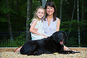 Mother and daughter sitting with their black lab