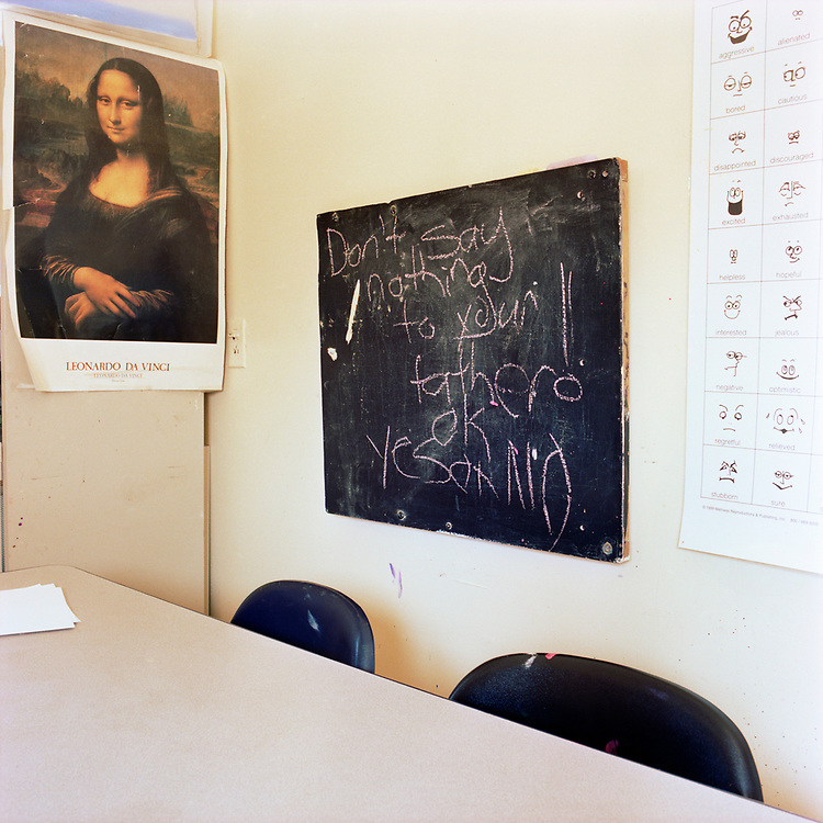 """A table and small blackboard in a cramped corner of a room, with a Mona Lisa poster and some sort of feelings / faces poster. On the blackboard """"Don't say nothing to your father! OK Yes or No"""" is written in big letters.  Two black plastic chairs are against the table."""