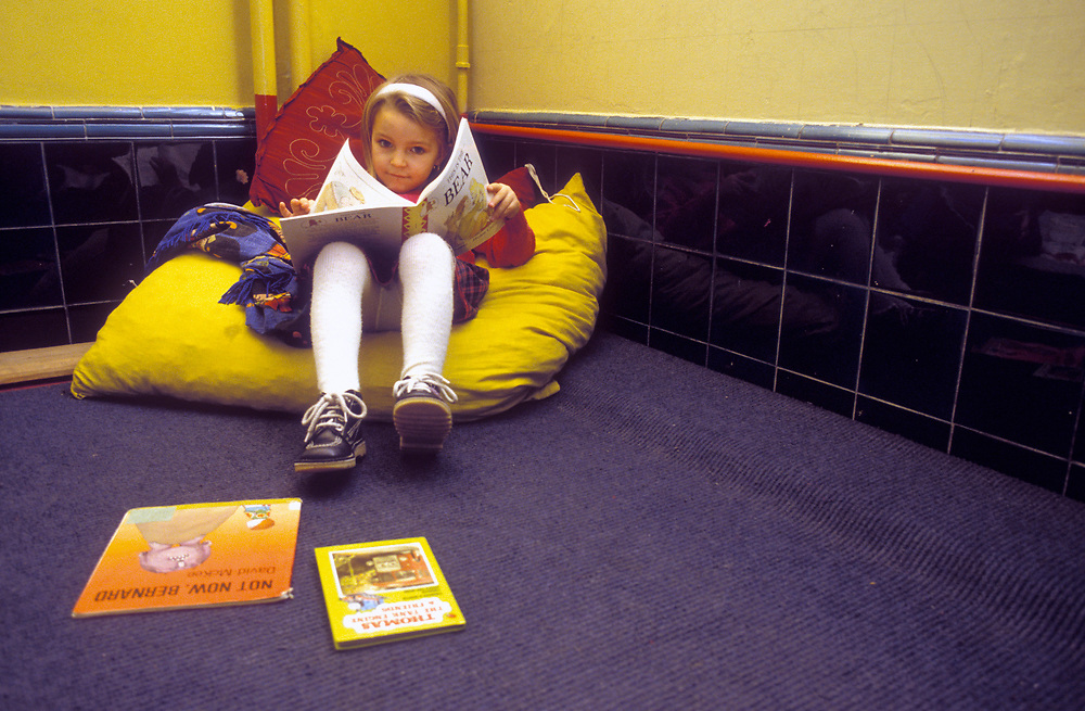 Girl reading book on big pillow in corner of classroom,