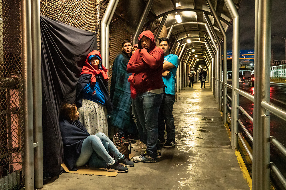A group of people seeking asylum from Venezuela sit in the cold and wait to cross the US border from Reynosa, Mexico January 26, 2019. The Trump administration plans to begin sending some asylum seekers back to Mexico to await the resolution of their immigration processing this week, Department of Homeland Security officials said Thursday. Photo by Ken Cedeno/UPI