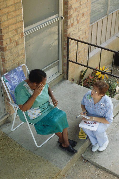 Anglo Democratic woman vists elderly African-American woman at her home in low-income neighborhood in Austin, Texas. ©Bob Daemmrich