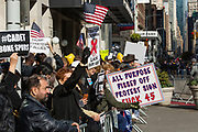 """New York, NY - 11 November 2019. New York City's Veterans Day Parade, today marking the 100th anniversary of the armistice ending the fighting of the first World War, was attended by a number of people protesting President Trump, who spoke at the opening ceremony, and a smaller number of pro-Trump supporters. Potest signs include """"All  Purpose Pissed Off Protest Sign Fuck 45,"""" """"Traitor Criminal Lock Him Up,"""" """"Trump: Betrayer of Allies,"""" and """"#Cadet Bone Spurs."""""""