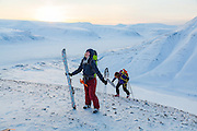 Michelle Blade (front) and Mylène Jacquemart reach a small summit at sunset in Koslådalen, Svalbard.
