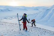 Michelle Blade (front) and Mylène Jacquemart reach a small summit at sunset in Koslådalen, Svalbard.