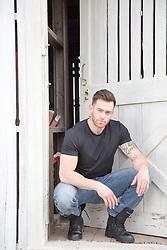muscular man sitting by a rustic barn