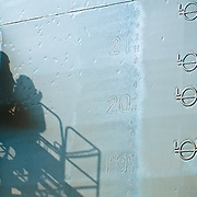 Scenes from a ship yard in Dubai. Siloutte of a worker spray piantin a ship.
