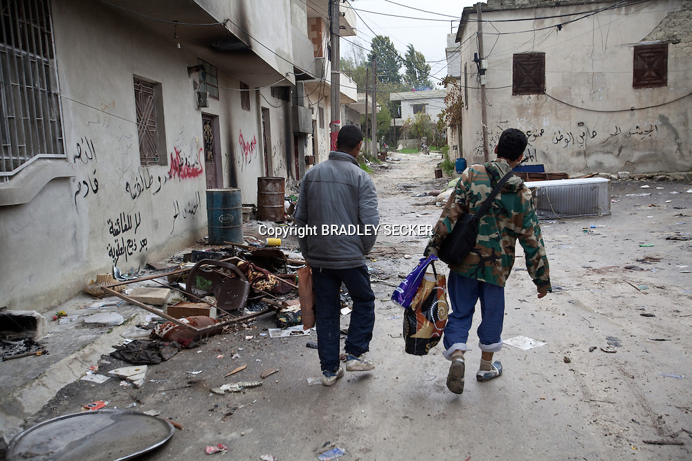 Syrians walk through a destroyed pro-regime village on the Turkish border, now deserted after the residents were said to have left after the surrounding area of Jisr al Shigour countryside was liberated. Rural Idlib, Syria. 24/11/2012
