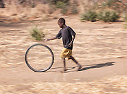 A young boy of the Nuba tribe plays with an old bicycle wheel, rolling it along the ground, in the village of Nyaro, Kordofan region