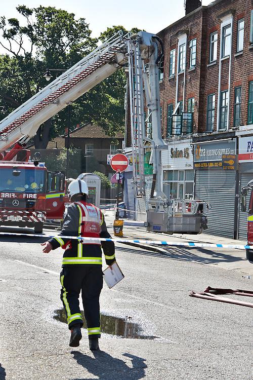 © Licensed to London News Pictures.  10/07/2013. LONDON, UK. General view of the scene of a fatal fire in flat above a shop on New Heston Road (Church Road), Hounslow. Two men and a woman jumped from the building before fire crews arrived. The woman, thought to be 30 years old, died at the scene and another body was discovered inside. Photo credit: Cliff Hide/LNP