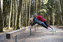 Couple doing push-ups on fitness trail in nature