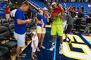 Glory Johnson of the Dallas Wings introduces one of her twins to fans after losing to the Connecticut Sun during a WNBA preseason game in Arlington, Texas on May 8, 2016.  (Cooper Neill for The New York Times)