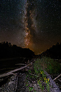 The Galactic Center of the Milky Way sets over the Carrabassett River of northern Maine in late August.  The Galactic Center is the rotational center of the Milky Way and where it appears brightest. It is 26,490 light years away from Earth in the direction of the constellation Sagittarius. The Milky Way is the second-largest galaxy in our Local Group, with its stellar disk approximately 100,000 light years in diameter and, on average, approximately 1,000 light years thick. The Milky Way is approximately 1.5 trillion times the mass of the Sun. To compare the relative physical scale of the Milky Way, if our Solar System out to Neptune were the size of a US quarter (24.3 mm; 0.955 in), the Milky Way would be approximately the size of the entire contiguous United States.  The Milky Way It is estimated to contain 100–400 billion stars and more than 100 billion planets.<br /> <br /> This image is a focus stack of 3 photographs where the foreground was briefly illuminated with a headlamp during each 20 second exposure.