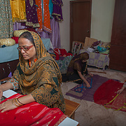INDIVIDUAL(S) PHOTOGRAPHED: Fakhira Anwar. LOCATION: Khurramabad, Landhi, Karachi, Pakistan. CAPTION: Fakhira Anwar stiches fabric using a sewing machine at her small in-house stitching workshop in Karachi, Pakistan. Fakhira has been stitching for the past 15 years. A housewife with three children, she started her home-based stitching business in 2006 when she got her first microfinancing support of Rs. 20,000 (£140) from the First Micro Finance Bank (FMFB). She has since been through several cycles of financing, and each time she has successfully paid back what she borrowed to the bank from her business revenue. Over time, she has been able to scale her business, and thus her income. Her most recent loan was Rs. 200,000 in July 2017. Today, she earns an average of Rs. 40,000 per month from this business. Fakhira's dream is to purchase an automated stitching and designing embroidery sewing machine; this will cost her Rs. 500,000.
