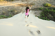 Young girl plays on a sand dune