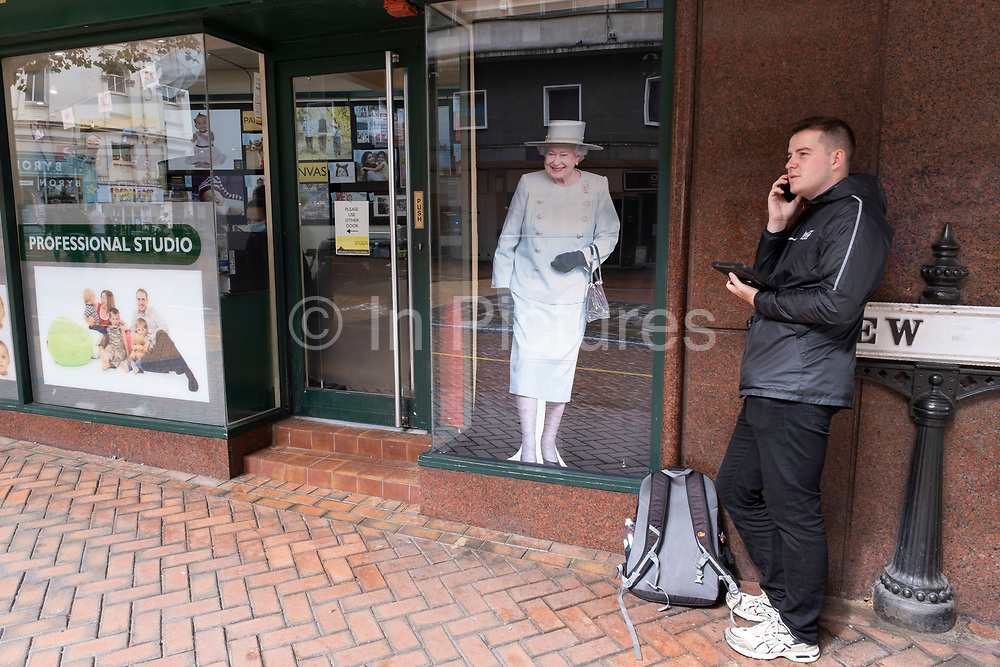 Cut out print of Her Majesty Queen Elizabeth II looks out from a printing shop in the city centre interacts with a passer by on his smart phone and tablet as a worker inside engages with her job on 18th August 2020 in Birmingham, United Kingdom.