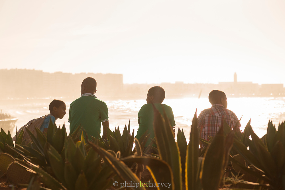 Children sitting at corniche and chatting at sunset, Casablanca, Morocco