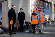 Bond Street guides holding orange-themed brolleys stand next to two construction site workmen. Mimicking the orange of the umbrellas and that of the hi-vis tabards, we see a coincidental urban scene in the week before Christmas. The guides stand on the street corner available to pass on retail information for visiting buyers as London is eager to encourage the spending of foreign money.