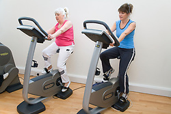 Women working out on exercise bikes at a gym,
