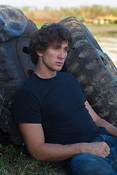 twenty something year old man with curly brown hair wearing a black tee shirt and jeans sitting up against large tires