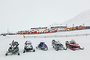 Snowmobiles parked in a row outside UNIS in Longyearbyen, Svalbard.