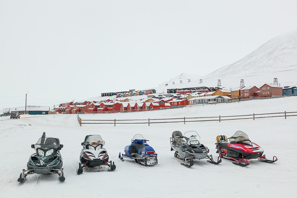 Snowmobiles parked in a row outside UNIS in Longyearbyen, Svalbard.