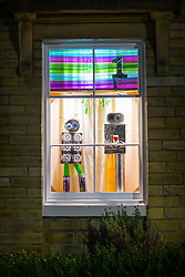 © Licensed to London News Pictures. 02/12/2016. Saltaire UK. The first of this years Advent windows have opened in the World Heritage village of Saltaire in Yorkshire. Each year windows in Saltaire homes are illuminated with a festive scene with one scene being opened daily from the 1st of December until the 24th of December. Photo credit: Andrew McCaren/LNP
