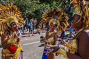 Dancers relax as they prepare for the parade - The Monday of the Notting Hill Carnival. The annual event on the streets of the Royal Borough of Kensington and Chelsea, over the August bank holiday weekend. It is led by members of the British West Indian community, and attracts around one million people annually, making it one of the world's largest street festivals.