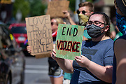 """A demonstrator holds a sign reading """"end violence"""" during the Mifflinburg Pride Event."""