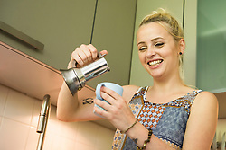 Beautiful young woman pouring coffee in the kitchen and smiling, Munich, Bavaria, Germany