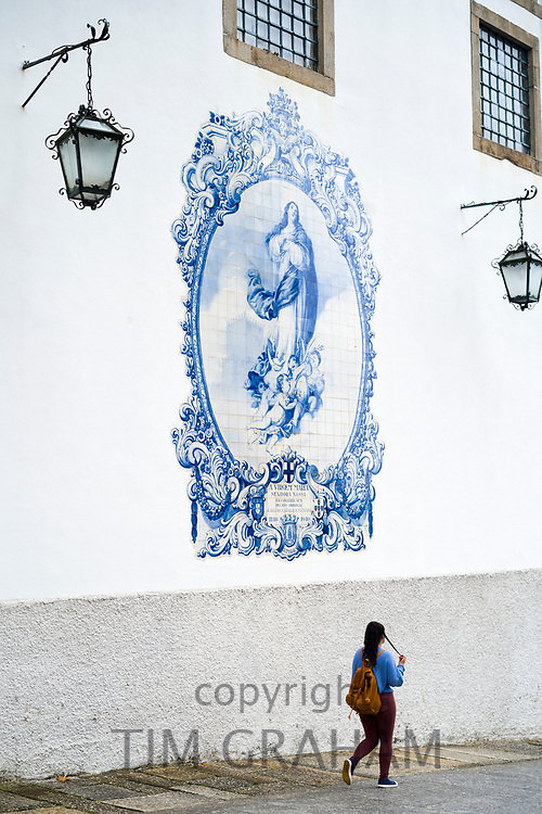 Young woman passing blue and white azulejos ceramic tiles of Convent Church of Carmo in Guimaraes in Northern Portugal