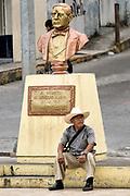 A Mexican sits under a bust of Benito Juarez in Papantla, Veracruz, Mexico.