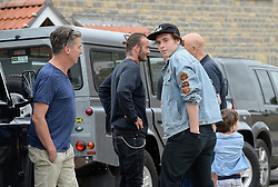 David Beckham (second left), Brooklyn Beckham (centre front), Michael Eavis (obscured right) and his grandson Noah celebrate a completed housing development in Pilton village in Somerset.